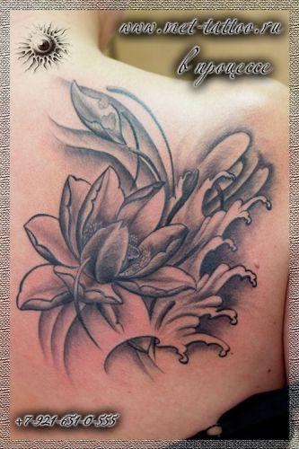 Женская черно-белая татуировка на лопатке.