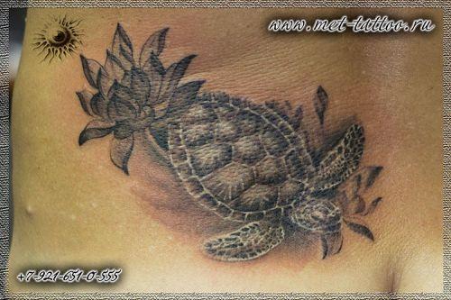 Черно-белая женская татуировка на пояснице. Морская черепаха в лотосах.