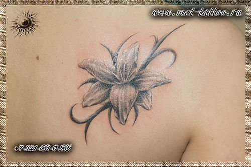 Фото татуировки на лопатке у девушки. Женская черно-белая татуировка - цветок с орнаментом.